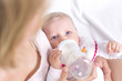 canvas print picture - Blonde Mutter gibt ihrer Tochter das Fläschchen