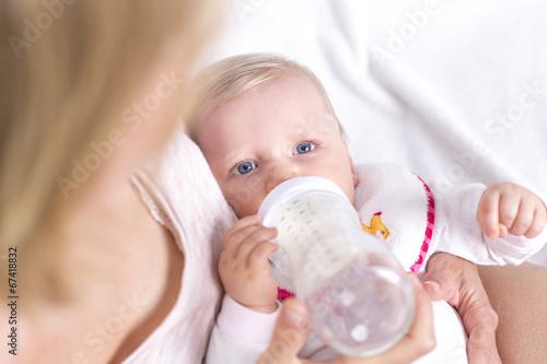 canvas print picture Blonde Mutter gibt ihrer Tochter das Fläschchen