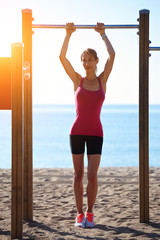 Attractive sporty woman at horizontal bar on the beach