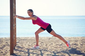 Female runner doing stretching exercise on the beachh