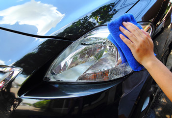 Hand with a microfiber wipe the car polishing.