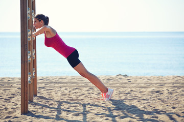 Athletic sporty woman pulls up on the horizontal bar