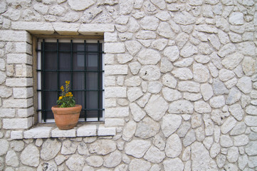 pot on the window on the wall of stones