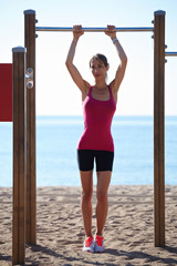 Athletic woman standing on the beach at horizontal bar