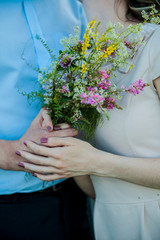 wedding: Bride and groom holding hands with bouquet