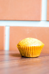 Banana cup cake on wood table at brick wall
