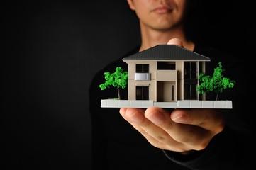 住宅模型を持っている男性と黒い背景