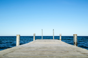 Low angle image of a wooden bath pier in blue water