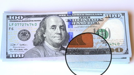 magnifying glass on corners of 100 dollars bill new