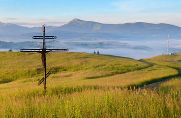 Cross-crucifix on the meadow at sunrise on the background of mou
