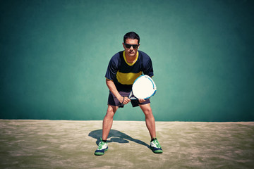 Athletic sportsman ready to feed ball in paddle game