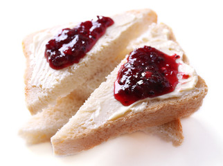 Fresh bread with blackcurrant jam and homemade butter, isolated