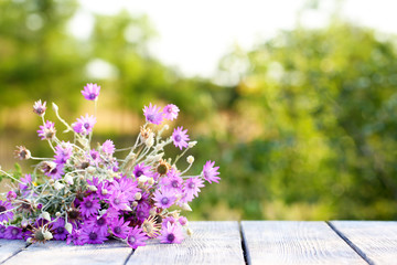 Beautiful wild flowers on table on bright background
