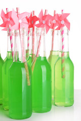 Bottles of drink with straw on light background