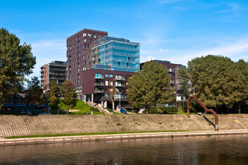 Modern Apartment Building across the River between Trees