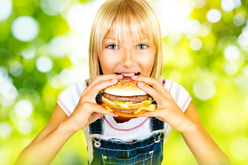 Pretty little girl eating a hamburger over nature background