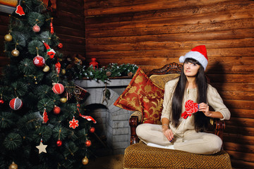 Girl with candy near Christmas tree