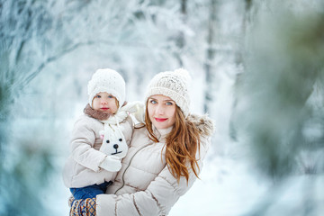 Mother holds daughter on hands in winter forest