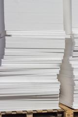 stacked white styrofoam sheets on wooden pallet