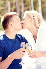 Kissing couple on the beach with champagne