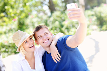 Young couple taking a picture of themselves at the beach