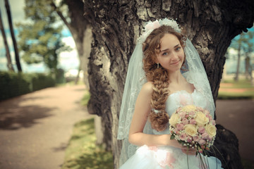 Portrait of beautiful bride in a park