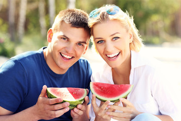 Happy couple with watermelon at the beach