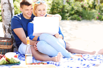 Happy couple with laptop at the beach