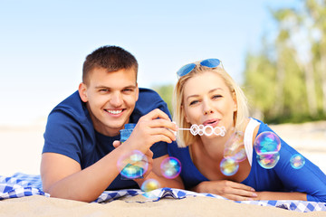 Young couple blowing bubbles at the beach