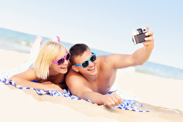 Happy couple taking pictures at the beach