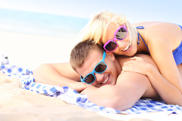 Joyful couple sunbathing at the beach