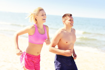 Young couple jogging along the beach
