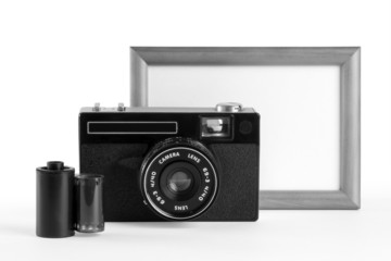 Old-fashioned film camera, film cassette and blank photoframe