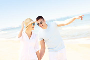 Cheerful couple walking along the beach