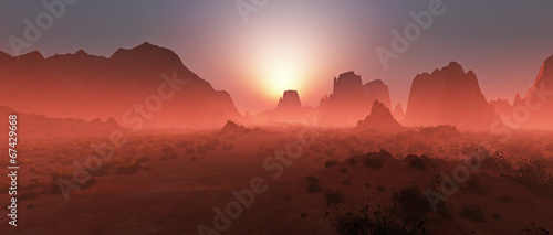 Leinwanddruck Bild Red rocky desert landscape in the mist at sunset. Panoramic shot