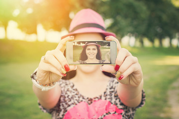 Pretty young woman taking a selfie in park on sunny summer day