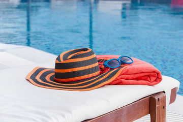 Sunbathing accessories on beach towel by a swimming pool