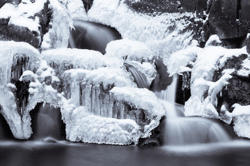 Half frozen waterfall in winter season in black and white