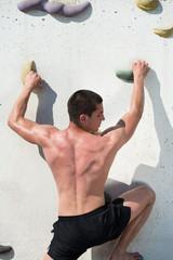 Young Man Climbing A Rock Wall