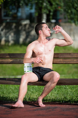 Young Muscular Man Drinking A Water Bottle