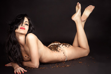 woman lying with coffee beans isolated on black background