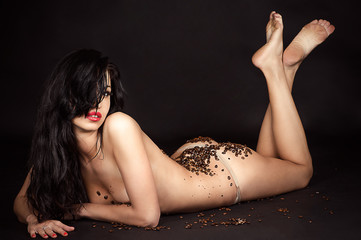 sexy woman lying with coffee beans isolated on black
