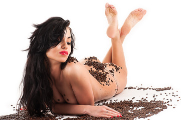 sexy woman lying with coffee beans isolated on white