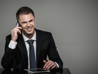 Well-dressed man in black suit with mobile phone and tablet pc