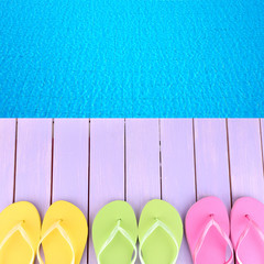 Colored flip flops on wooden platform beside sea