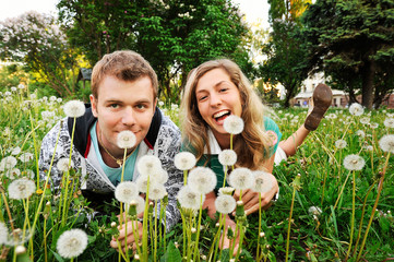 couple of young people laughing in the dandelions