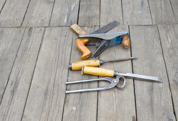Set of vintage carpenter tools on wooden floor.