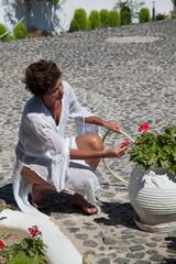 Donna che cura le piante in giardino