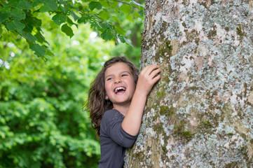 Kind umarmt lachend einen riesigen Baumstamm