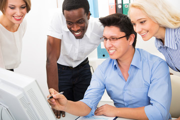 Happy business people gathered around laptop